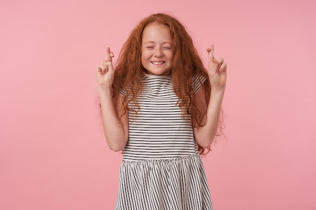 Studio photo of positive curly girl with long foxy hair standing over pink background with closed eyes, raising hands with crossed fingers, making wish with pleasant sincere smile