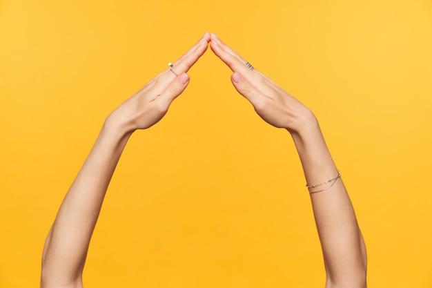 Studio fotografico di mani abbastanza ben curate di giovani femmine togather pieghevole mentre imita il tetto della casa, isolato su sfondo giallo. concetto di mani di donna