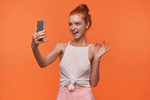 Foto di studio di donna abbastanza giovane con lettore con acconciatura panino in posa su sfondo arancione in top bianco e gonna rosa, tenendo lo smartphone in mano e guardando lo schermo con un sorriso gioioso