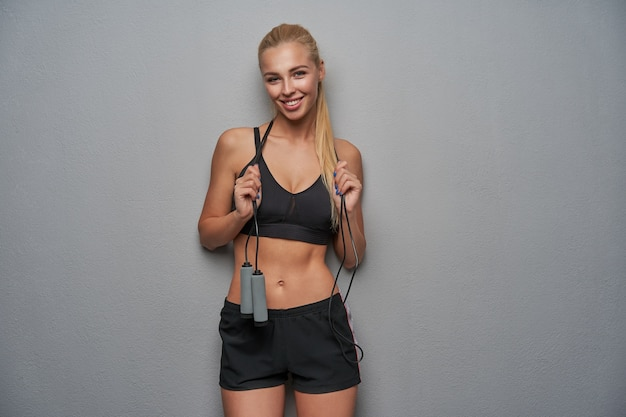Studio photo of pretty young sporty blonde woman looking positively to camera with charming smile, wearing black top and shorts, standing over light grey background with jump rope on her neck