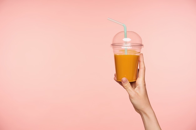 Studio photo of raised well-groomed woman's hand with nude manicure holding plastic cup of orange juice with straw while being isolated over pink background
