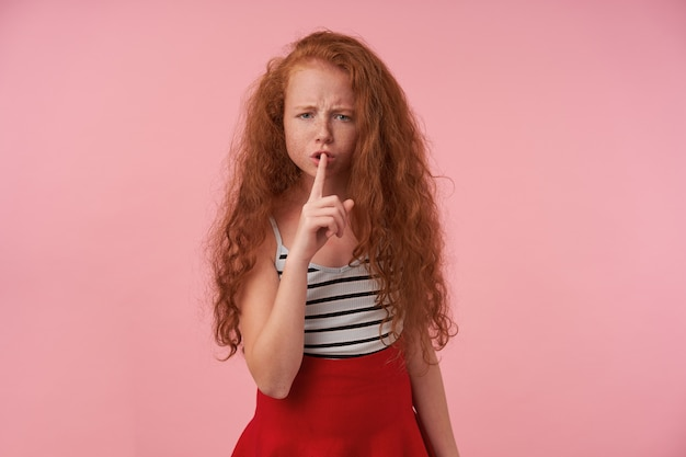 Studio photo of serious redhead girl with long curly hair wearing red skirt and striped top, keeping forfinger on her lips, frowning to camera and asking to keep silence, standing over pink background