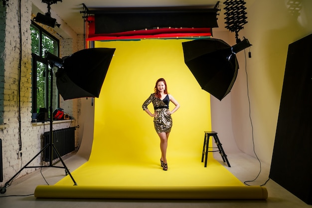 Studio photo session of a girl in a black dress on a yellow background