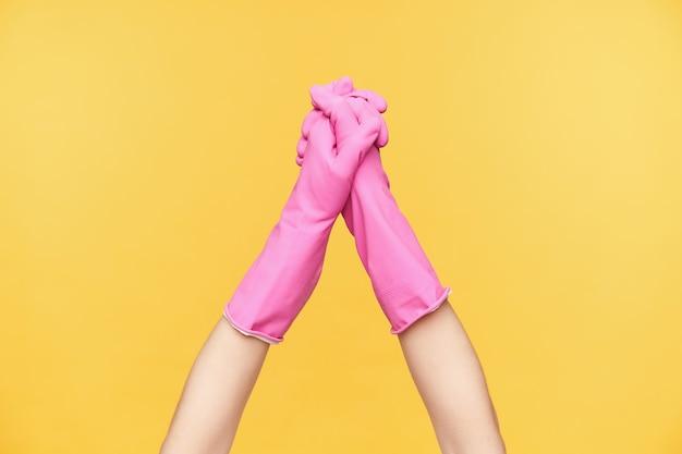 Foto di studio di due mani in guanti rosa che si piegano insieme mentre vengono sollevate, isolate su sfondo arancione. mani umane e concetto gesticolare