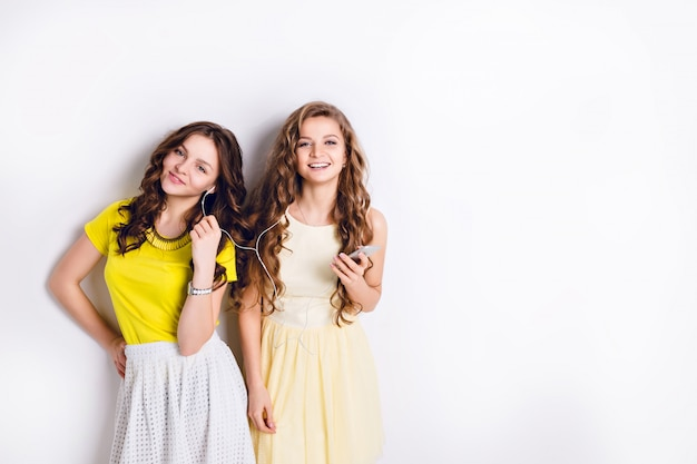 Studio photo of two standing smiling girls listening to music on a smartphone and having fun.