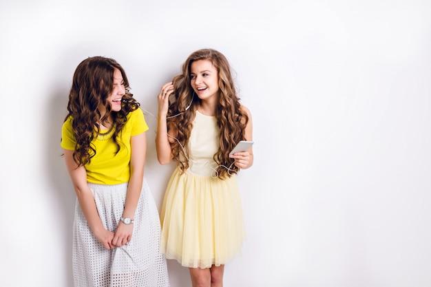 Foto di studio di due ragazze sorridenti in piedi che ascoltano la musica su uno smartphone e si divertono.
