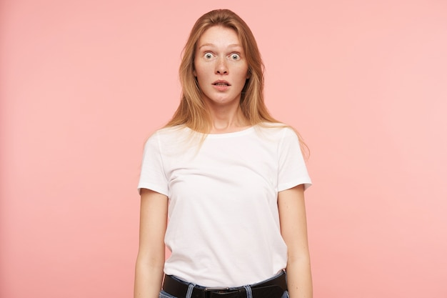 Studio photo of young amazed long haired redhead lady rounding surprisedly her green eyes while looking at camera, isolated over pink background in white basic t-shirt