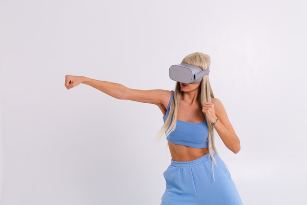 Studio photo of a young attractive woman in a warm blue fashionable suit wearing virtual reality glasses on a white plays a boxing fight