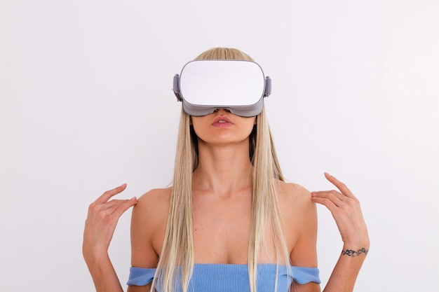 Studio photo of a young attractive woman in a warm blue fashionable suit wearing virtual reality glasses on a white