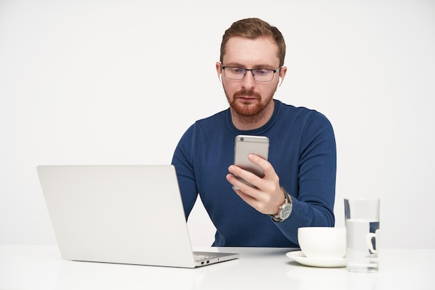 Studio photo of young fair-haired male in glasses keeping smartphone in raised hand and looking seriously on screen while reading message, posing over white background