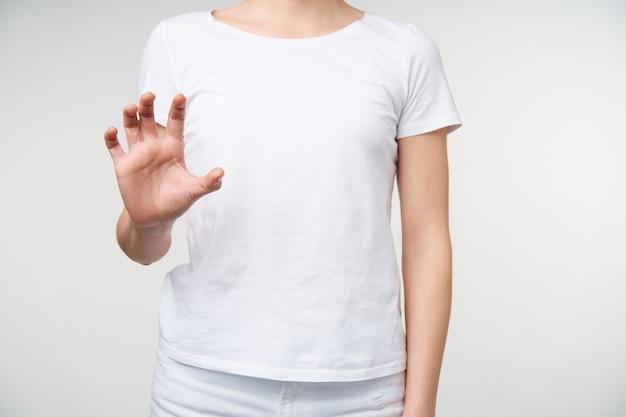 Foto di studio di giovane donna vestita in abiti casual, tenendo la mano alzata mentre usa il linguaggio dei segni per mostrare il fotografo di parole, in piedi su sfondo bianco