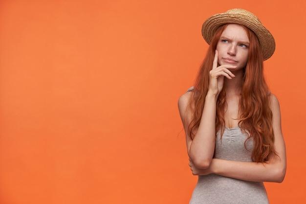 Studio foto di giovane donna con ondulati capelli foxy tenendo la mano sul mento, guardando da parte con la fronte accigliata, in posa su sfondo arancione in abiti casual