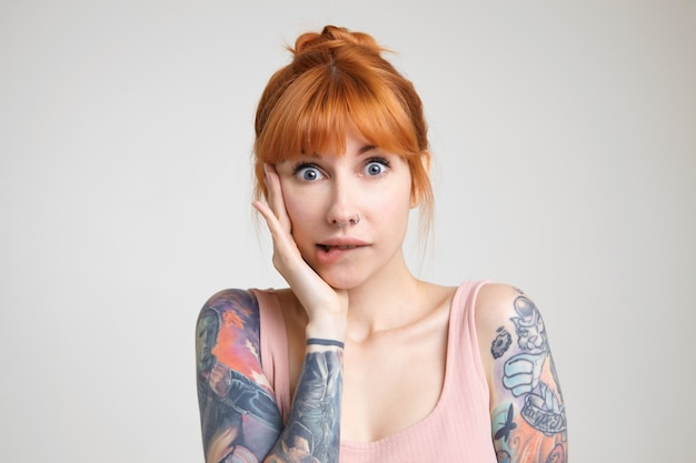 Studio photo of young green-eyed redhead tattooed woman biting underlip while looking confusedly at camera, keeping raised hand on her face while posing over white background