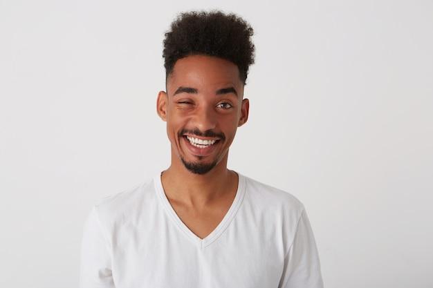 Foto dello studio di giovane uomo barbuto bello del brunette con il taglio di capelli alla moda che sorride felicemente