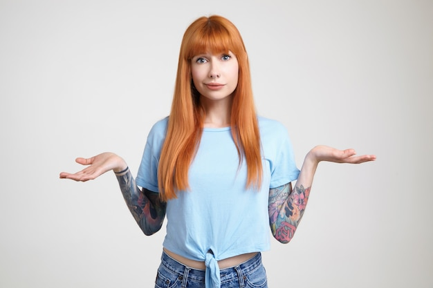 Studio photo of young long haired redhead lady with tattoos keeping her palms raised while looking confusedly at camera, isolated over white background