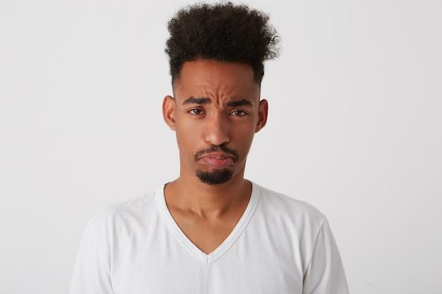 Foto di studio di giovane uomo bruna dalla pelle scura offeso con taglio di capelli alla moda che fa il broncio sulle labbra