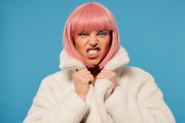 Studio photo of young pretty lady with short pink hair frowning her face and showing teeth while twisting her mouth, dressed in white faux fur coat while standing over blue background