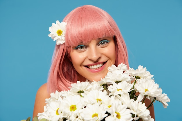 Studio photo of young pretty romantic pink haired woman with festive makeup posing in white flowers over blue background, looking positively at camera with charming smile