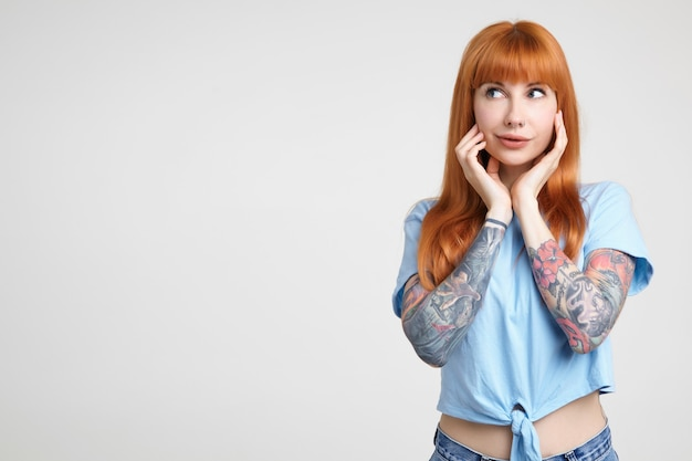 Studio photo of young pretty tattooed female with long foxy hair holding raised hands on her cheeks while looking wonderingly aside, isolated over white background