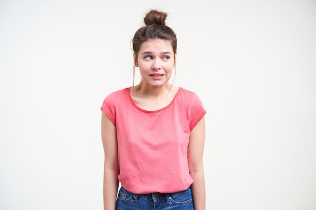 Studio photo of young puzzled brown haired female looking confusedly aside and keeping hands down while standing over white background in pink t-shirt