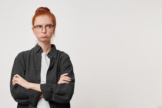 Foto di studio di una giovane studentessa rossa che è in piedi con le braccia conserte guardando di lato