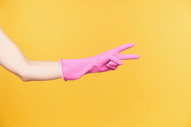 Foto dello studio della mano della giovane donna nel guanto di gomma che forma il gesto di vittoria con due dita mentre è isolato sopra fondo arancio. segni e concetto gesticolare