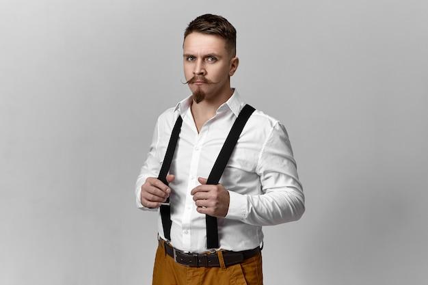 Foto di studio di attraente elegante giovane sposo con baffi a manubrio e barba vestirsi