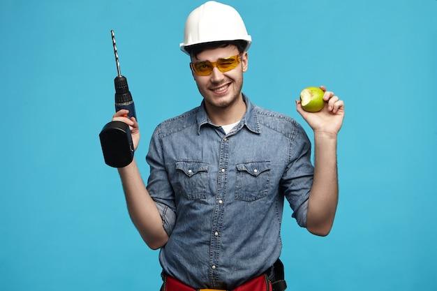 Foto di studio di laborioso bel giovane tuttofare indossando elmetto protettivo e occhiali in posa