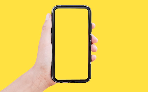 黄色の背景に、男性の手でスマートフォンのスタジオ画像。
