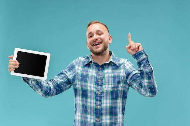Studio picture of positive man isolated on blue wall standing in casual clothes holding tablet and showing it blank screen with happy smile