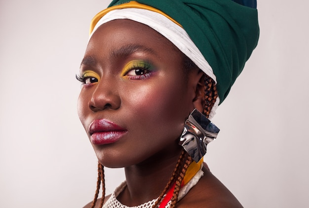 Studio portrait of african young woman with vibrant makeup of yellow and green colors. colorful ethnic headwrap.