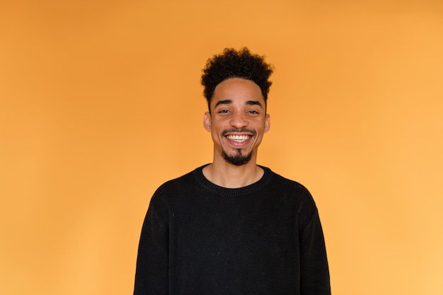 Studio portrait of afro american man wearing black pullover smiling over orange wall.