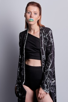 Studio portrait of attractive european model in high waisted briefs, short blouse and black coat with print