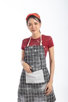 스튜디오 초상화 매력적인 젊은 여자는 앞치마를 입고 흰색 배경에 빵집을 만드는
