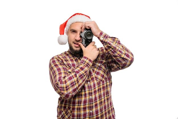 Studio portrait of bearded man wearing santa hat holding a retro camera, making a photo. isolated white background