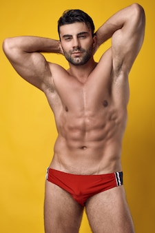 Studio portrait of a beautiful brutal tanned muscular man wearing a red underwear on a yellow