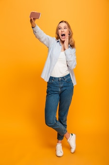 Studio portrait of beautiful excited woman smiling and photographing herself on smartphone, isolated over yellow space