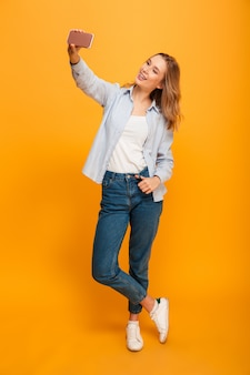 Studio portrait of beautiful woman smiling and taking selfie photographing herself, isolated over yellow space