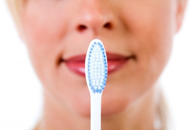 Studio portrait of beautiful young woman posing with toothbrush