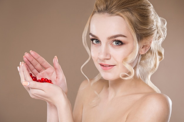 Studio portrait of a blonde in her hands red capsules of vitamins
