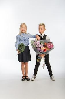 Studio portrait boy gives girl festive bouquet, congratulatory concept, white background, copy space