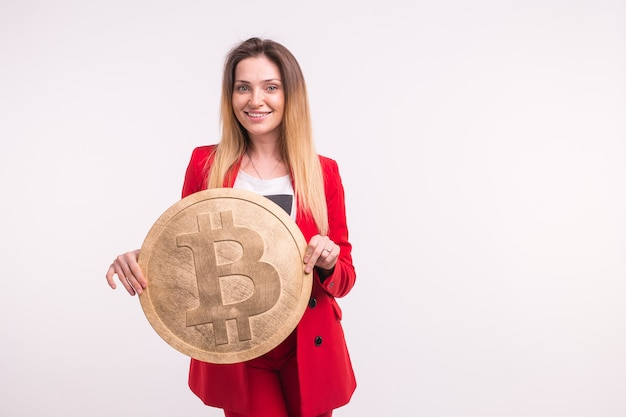 Studio portrait of business lady in red suit with bitcoin on hands