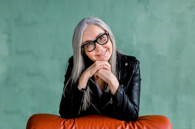 Studio portrait of charming senior modern lady in eyeglasses, with long straight gray hair, wearing trendy black leather jacket, which posing on camera with smile