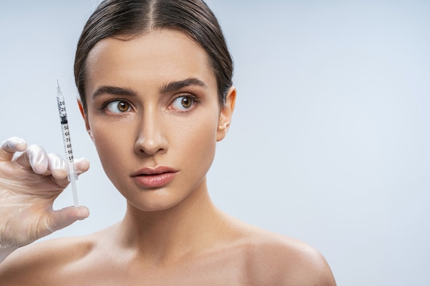 Studio portrait of charming young clean fresh face beautiful brunette female holding syringe with filler