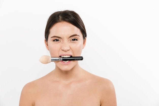 Studio portrait of cheerful asian woman being half-naked and makeup brush, in her mouth, isolated over white
