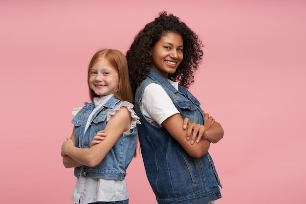 Studio portrait of cheerful pretty young girls leaning on each other and smiling happily with broad smiles, keeping hands folded while posing on pink