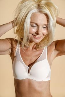 Studio portrait of confident caucasian mature blonde female model in white lingerie smiling