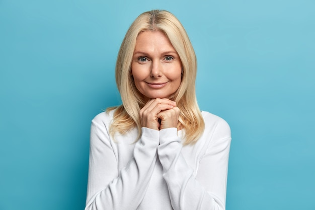 Studio portrait of confident fifty years old woman keeps hands under chin looks directly at camera with calm expression wears white sweater has well cared skin poses