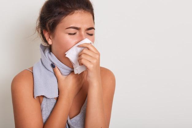 Studio portrait of cute unhealthy caucasian female with paper napkin sneezing