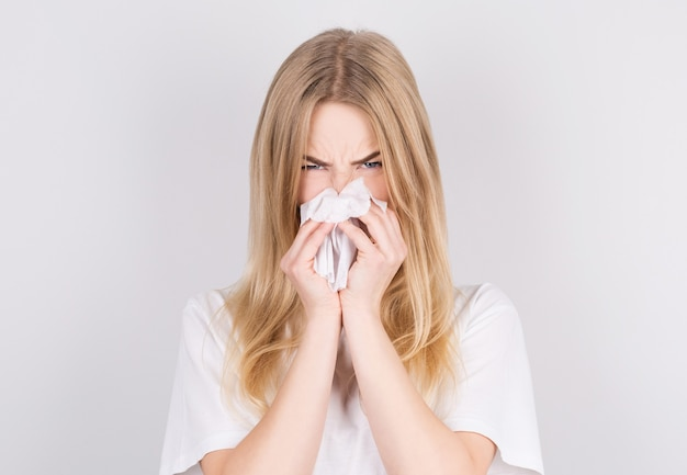 Studio portrait of cute unhealthy caucasian woman with paper napkin sneezing due to allergy, flu or cold